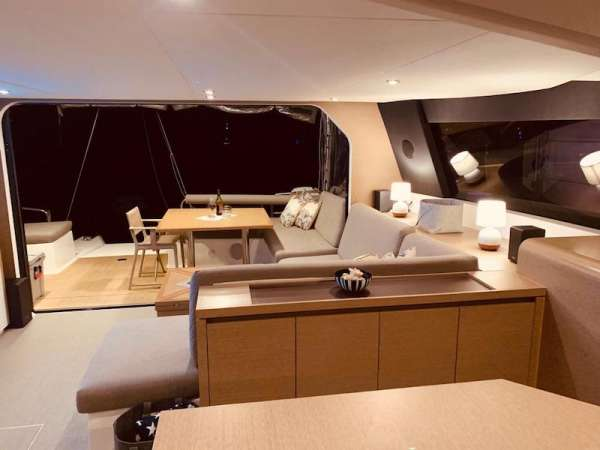Outdoor - a pair of couches covered by a hard bimini - outdoor galley with fridge, grill and sink and a teak table with seating for 8.