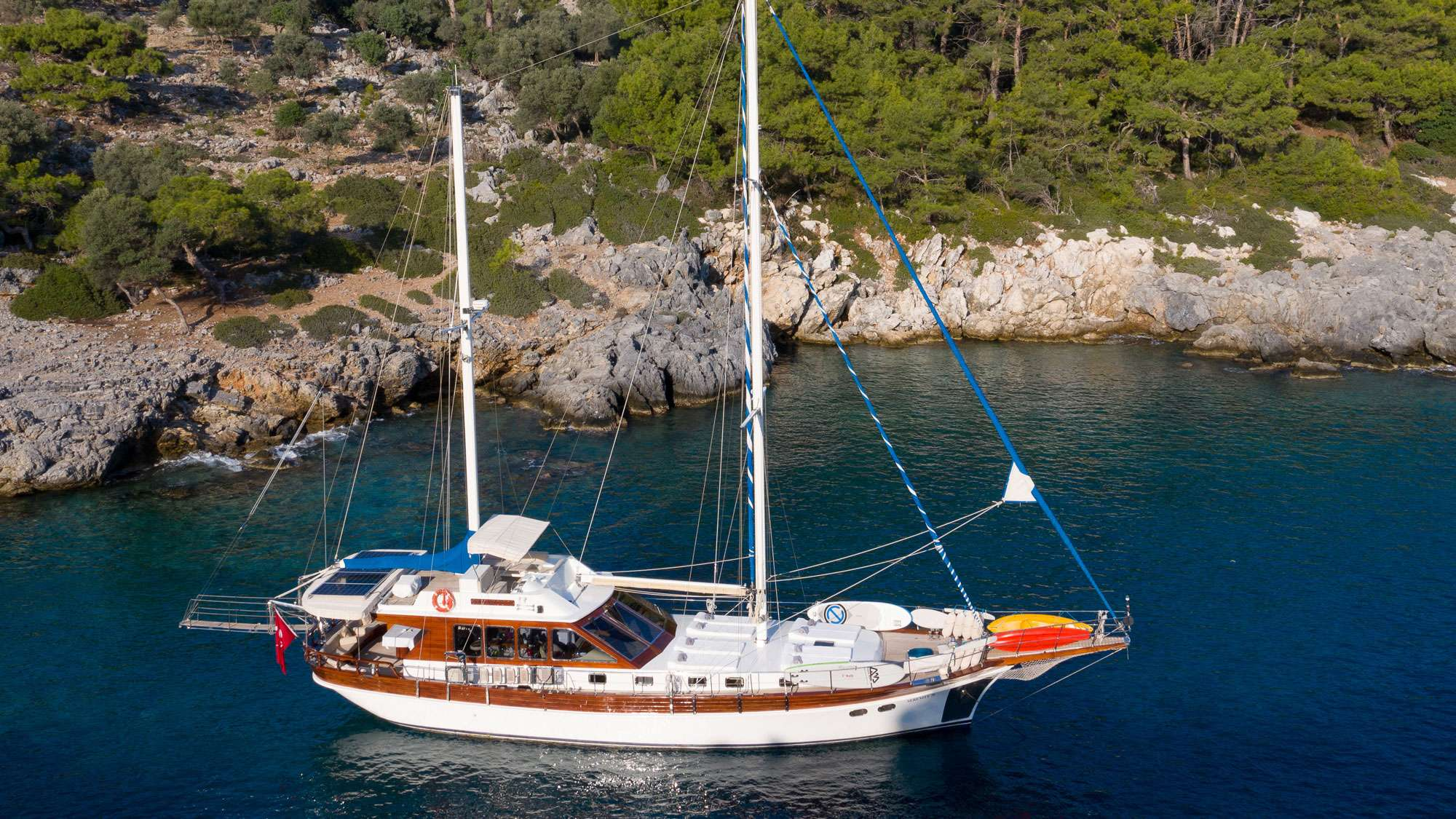 In current times when the industry is concentrating more and more on larger yachts, Serenity 70 is one of the few motor sailers that is available for charter in the East Med which is modest in size and budget without compromising on luxury and comfort. She has a very cosy honeymooner master cabin with a white interior and four portholes that flood in reflections from the sea. The remaining two double cabins are smaller in size and ideal for children or younger adults, though throughout her charter history this vessel has successfully accommodated six adults during many charters. Taking into consideration that guests will spend almost all their time outdoors, the limited space of the two double cabins is over shadowed by the comfortable aft dining area, inviting flybridge, ideal forward sun tanning area and the variety of amenities and water toys that you would normally only find aboard much larger vessels. The salon is very functional and includes a traditionally designed bar area with high seats facing panoramic views of the outside that is just perfect for enjoying an evening drink with friends and crew.