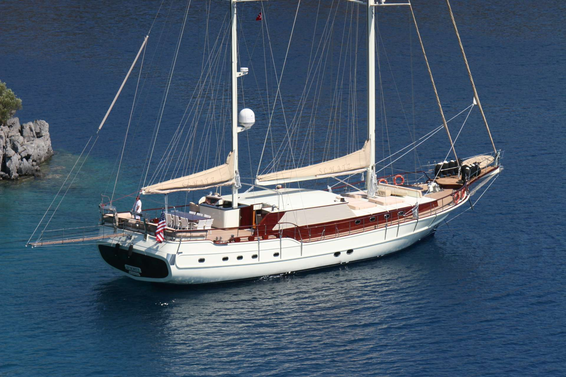 SCHATZ made her maiden voyage in 2005 and went through a comprehensive refit for her interior, exterior and machinery in 2013. She offers immense volume in her cabins due to her flat transom where the master cabin is located, beautifully decorated by large port holes facing straight at the sea bed. There is a VIP cabin located in the forward section, almost equal in size to the aft master, and three other double cabins, making this yacht ideal for groups up to 10 guests. Upon entering the vessel, it is a natural instinct to drop your bags on deck and lay down on the inviting full beam lounge cushions. The spacious and bimini protected aft dining table is supported by a fully stocked bar with all the amenities. You will find all the modern comforts on board including wifi, cable TV, games and plenty of water sports that can be enjoyed to its fullest thanks to the tender with a powerful 115hp outboard engine. With plenty of deck space for sun tanning in all sections, a powerful air conditioning system and a wonderful crew, this is the perfect yacht to enjoy a relaxing time at sea.