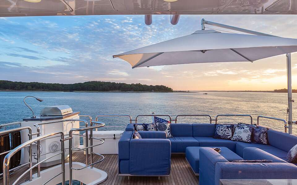 The flybridge features a large grill along with seating area and large sun umbrella for shade and protection.